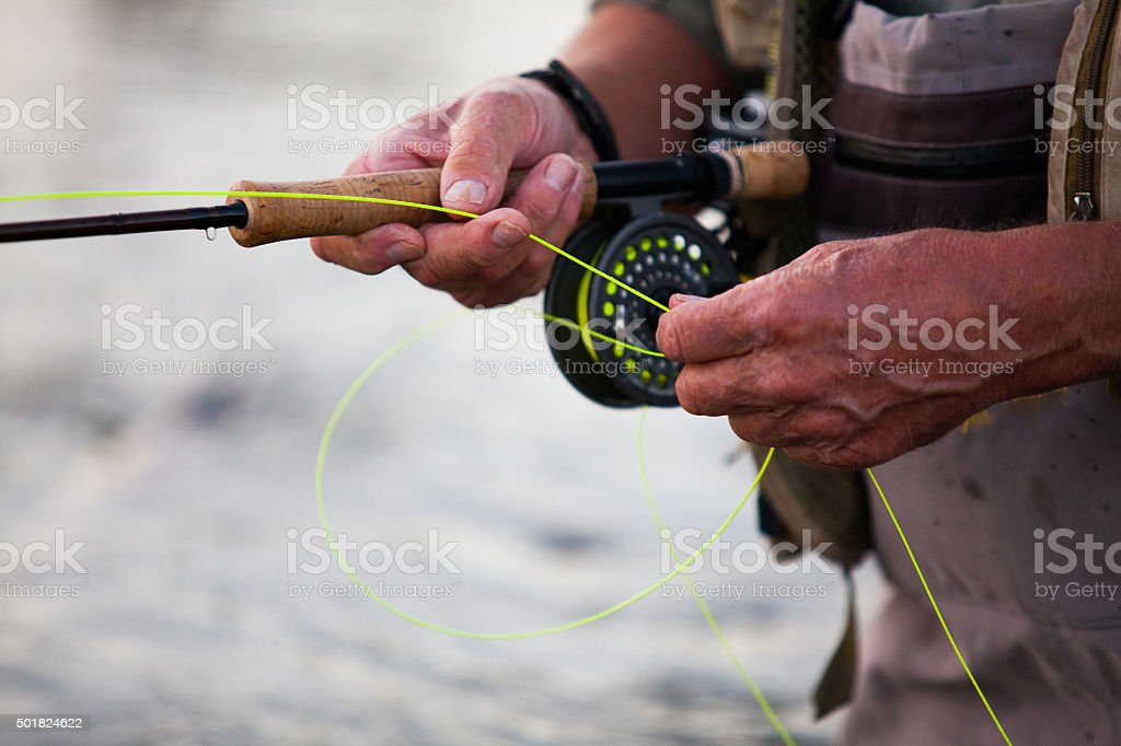 Elderly man fly fishing in a river stock photo