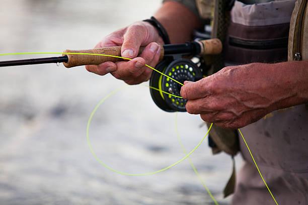 homem idoso pesca de trutas em um rio - pescaria com iscas artificiais - fotografias e filmes do acervo