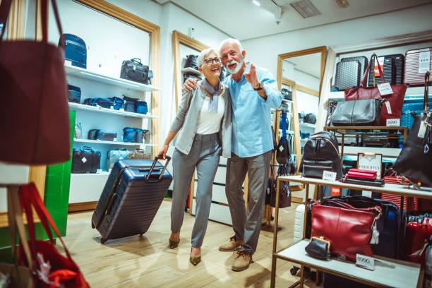 älterer mann deutete eine vorwärtsbewegung zu seinem partner bei der auswahl eines reise koffers im ladengeschäft taschen und accessoires - trolley kaufen stock-fotos und bilder