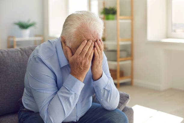 Elderly man, grieving about death of relative or forgotten by family, crying alone stock photo