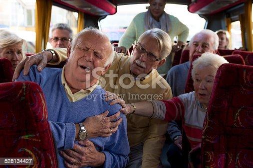 Elderly man having a heart attack on a coach.