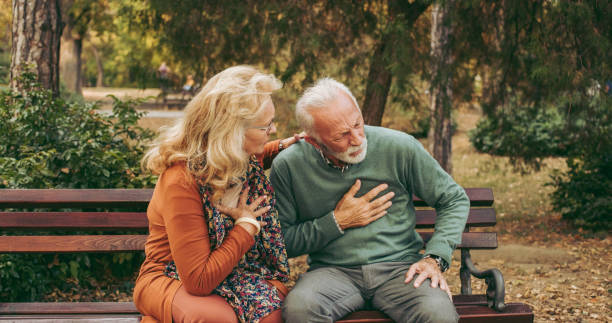 Elderly man having chest pains or heart attack in the park stock photo