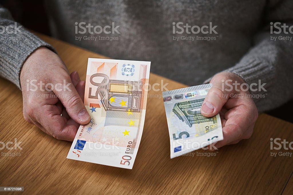 Elderly man holding a euro banknotes stock photo
