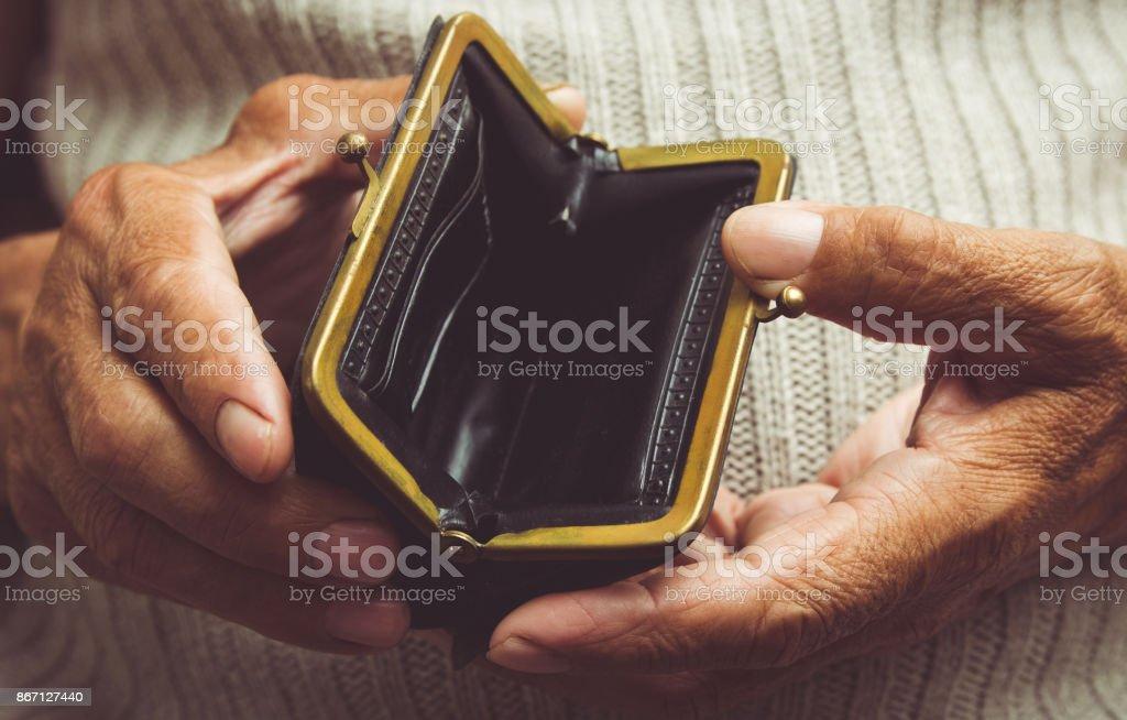 O homem idoso detém em suas mãos uma carteira vazia. Bolsa vazia do vintage nas mãos enrugadas. Pobreza no conceito de aposentadoria. Tonificação especial - foto de acervo