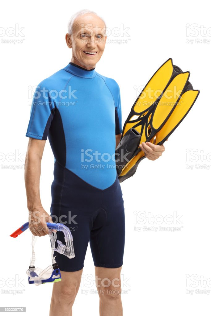 Elderly man in a wetsuit with snorkeling equipment stock photo