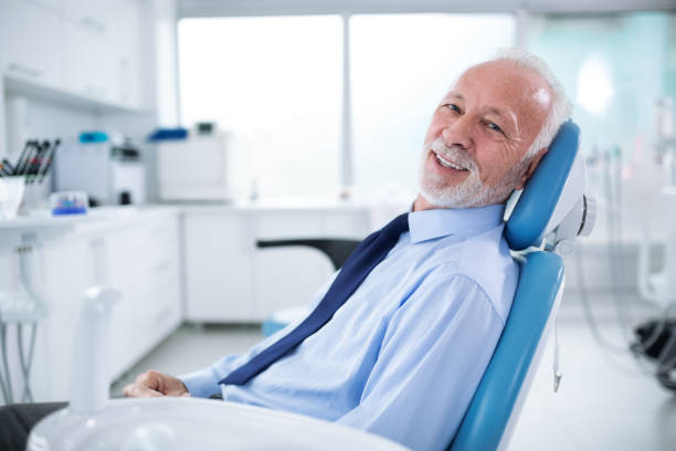 Elderly man in dentist's chair without fear waiting for treatment stock photo