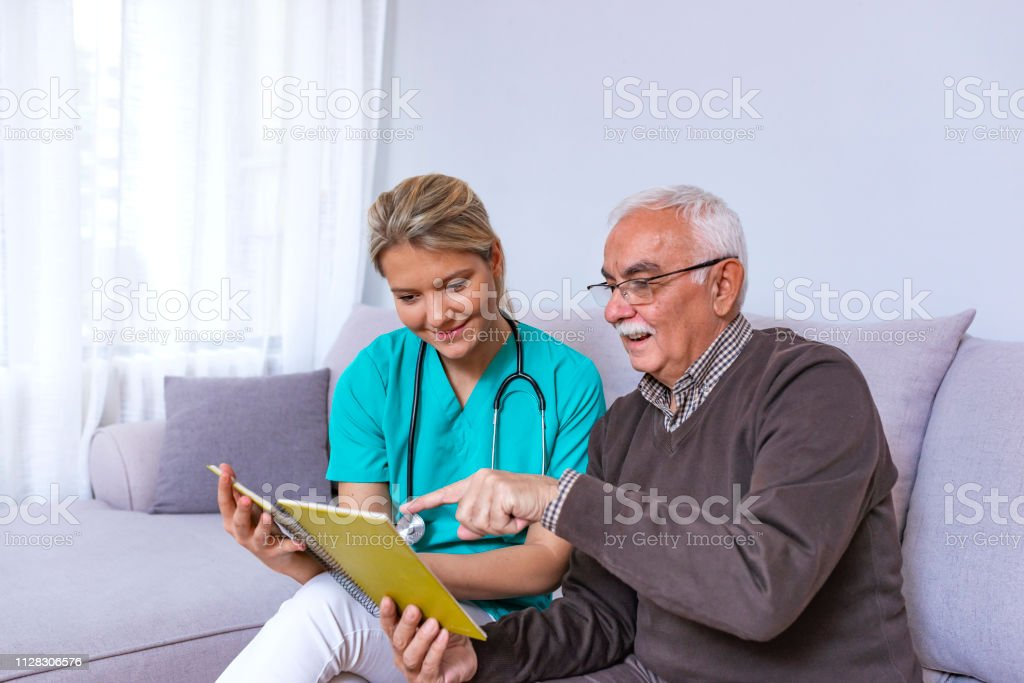 Man sitting on a couch, looking at a photo album and sharing fond...