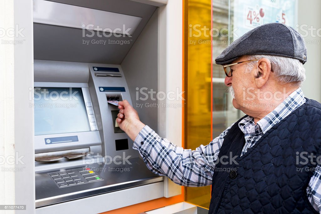 elderly man inserting credit card to ATM - foto de stock