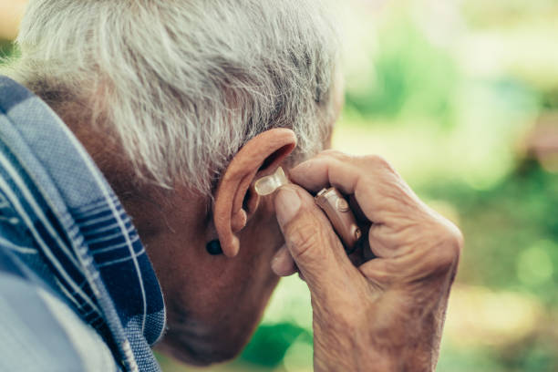 elderly man inserting his hearing aid - hearing loss stock pictures, royalty-free photos & images