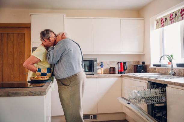 älterer mann küsst seine frau - emoticon hug stock-fotos und bilder
