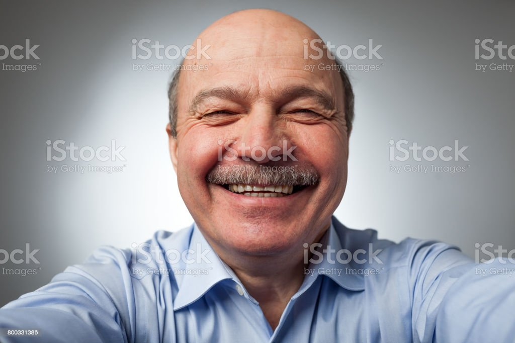 Elderly man laughs from ear to ear, giggles on the funny stories. stock photo
