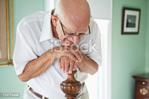 Elderly man (80s) at home leaning on bedpost, eyes closed looking upset.