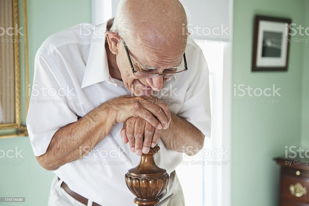 Elderly man leaning on bedpost, eyes closed stock photo