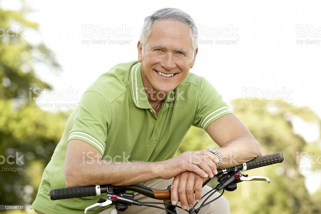 Elderly man leaning over bicycle handlebars smiling royalty-free stock photo