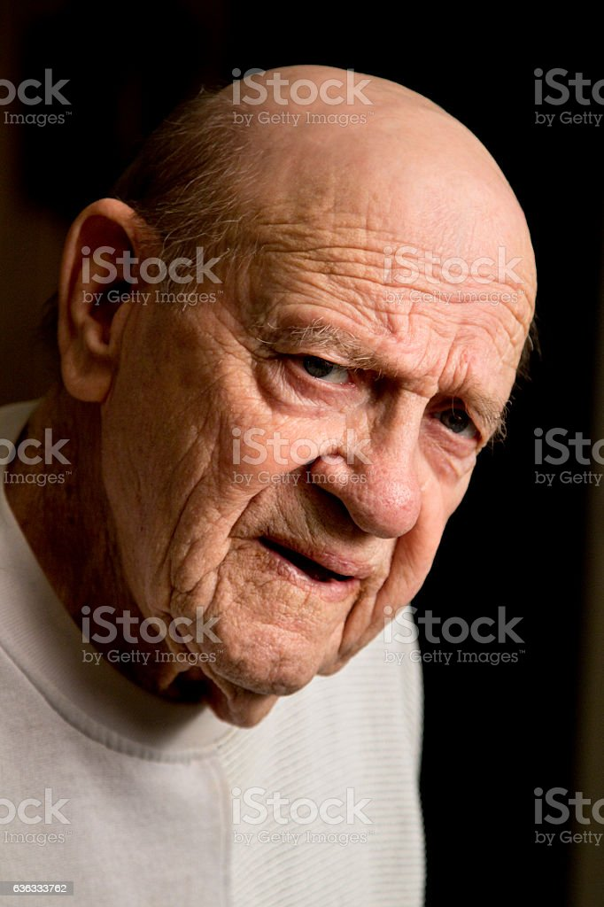 Elderly man looking in to camera with an unpleasant look stock photo