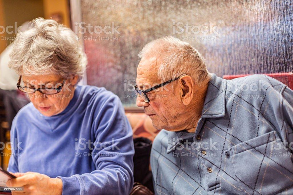 Elderly Man Looking To Daughter For Help Ordering Breakfast stock photo