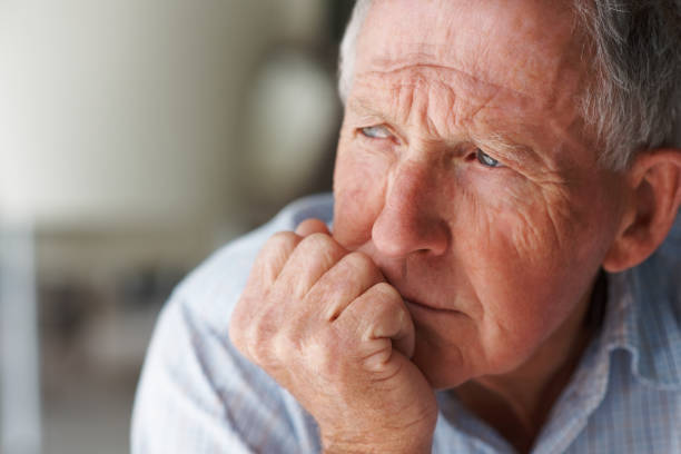 Elderly man lost in thought stock photo