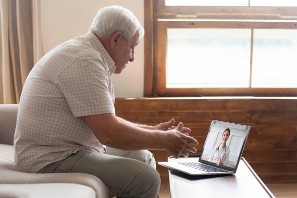 hombre de edad avanzada hacer videollamada distante comunicarse con el médico en línea - telehealth fotografías e imágenes de stock