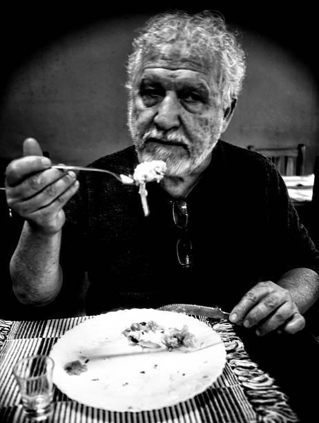 Elderly man making a meal in restaurant - foto de acervo