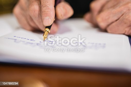 Close up of an older man writing something down on a piece of paper with pen