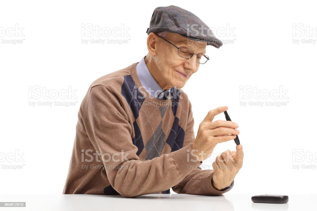 Elderly man measuring his blood sugar level with a glucometer royalty-free stock photo