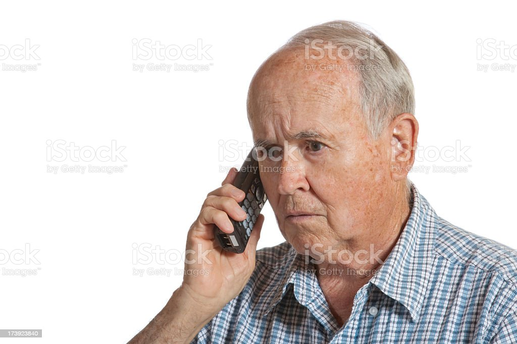 Elderly man on a cordless phone receiving bad news royalty-free stock photo