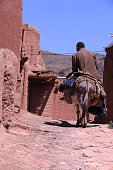 May 2019, Abyaneh, Iran. Farmer rides the donkey on the streets of red clay mountain village of Abyneh.