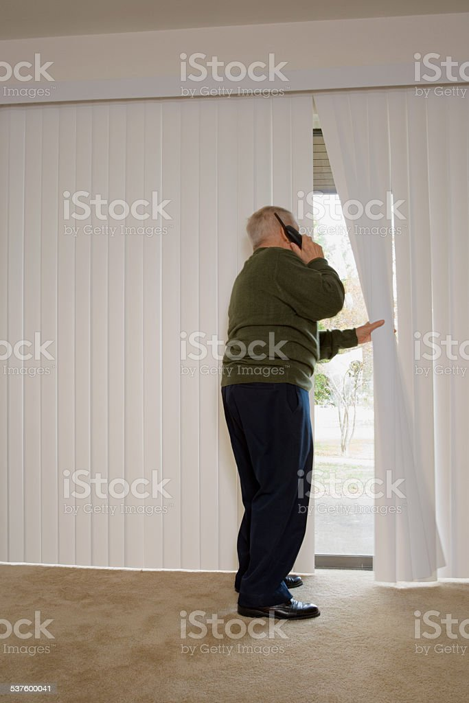 Elderly man on phone and looking out of window stock photo