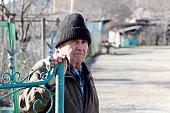 Elderly man opens the iron gate in rural yard