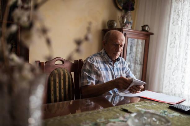 hombre mayor empacando su dinero de la pensión en un sobre - un solo hombre mayor fotografías e imágenes de stock