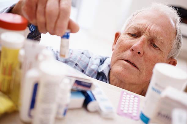älterer mann pflücken medizin-flasche von einem regal - lieblingsrezepte stock-fotos und bilder