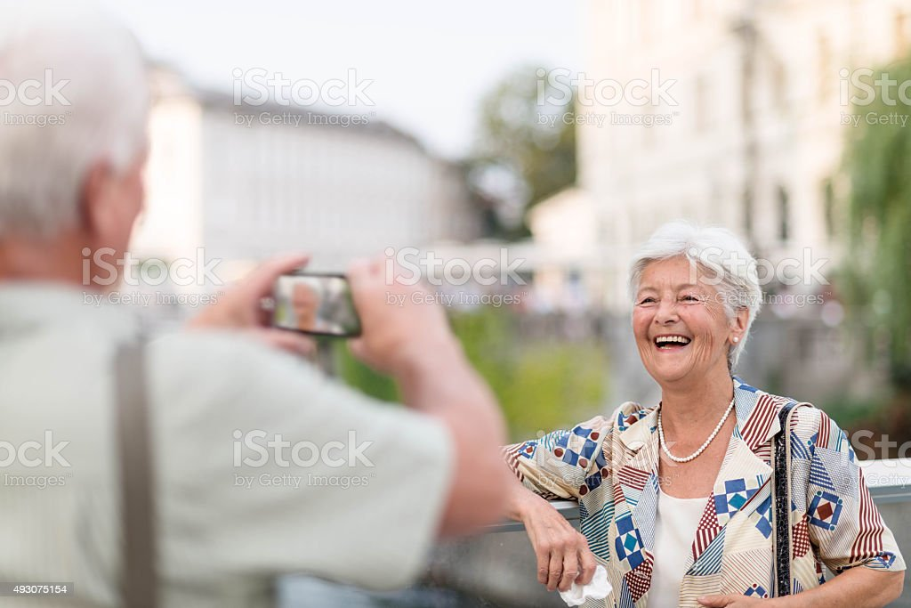 Elderly man picture his wife with smart phone stock photo