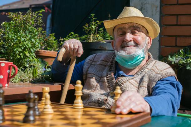 elderly man playing chess during coronavirus epidemic quarantine stock photo