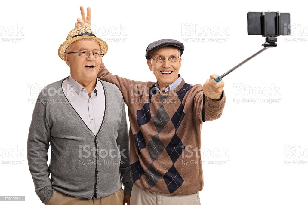 Elderly man pranking with bunny ears and taking a selfie stock photo