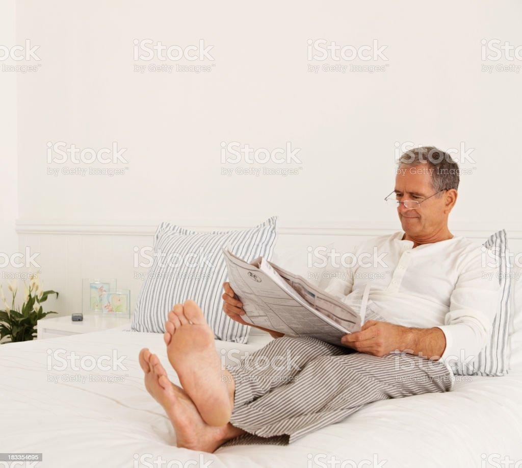 Älterer Mann liest Zeitung im Bett – Foto