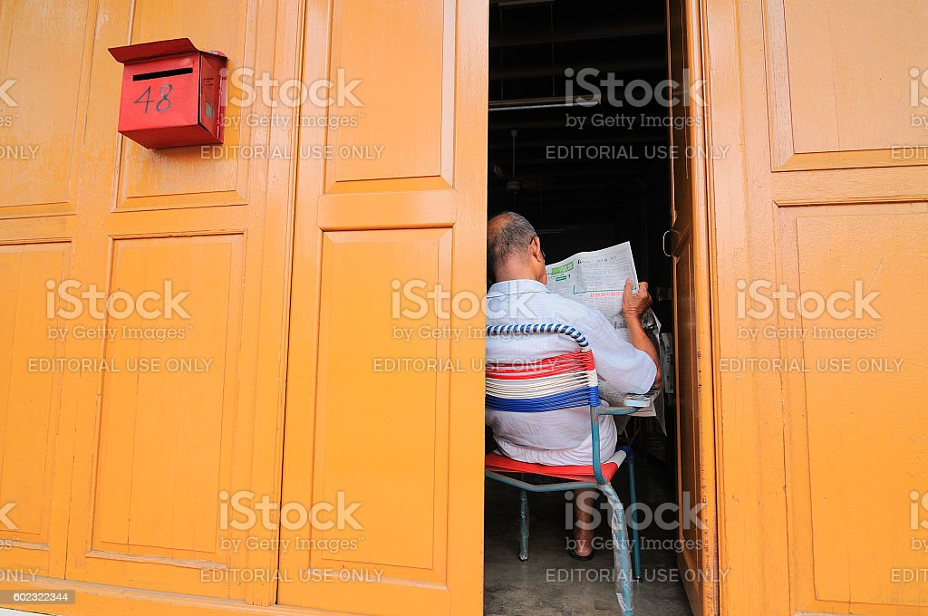 Elderly Man Reads The Papers From Behind Doors Melaka Malaysia Stock Photo  - Download Image Now