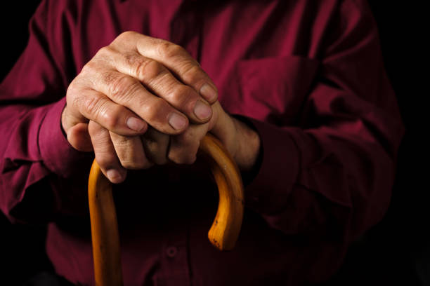 Elderly man resting his hands on his walking cane stock photo