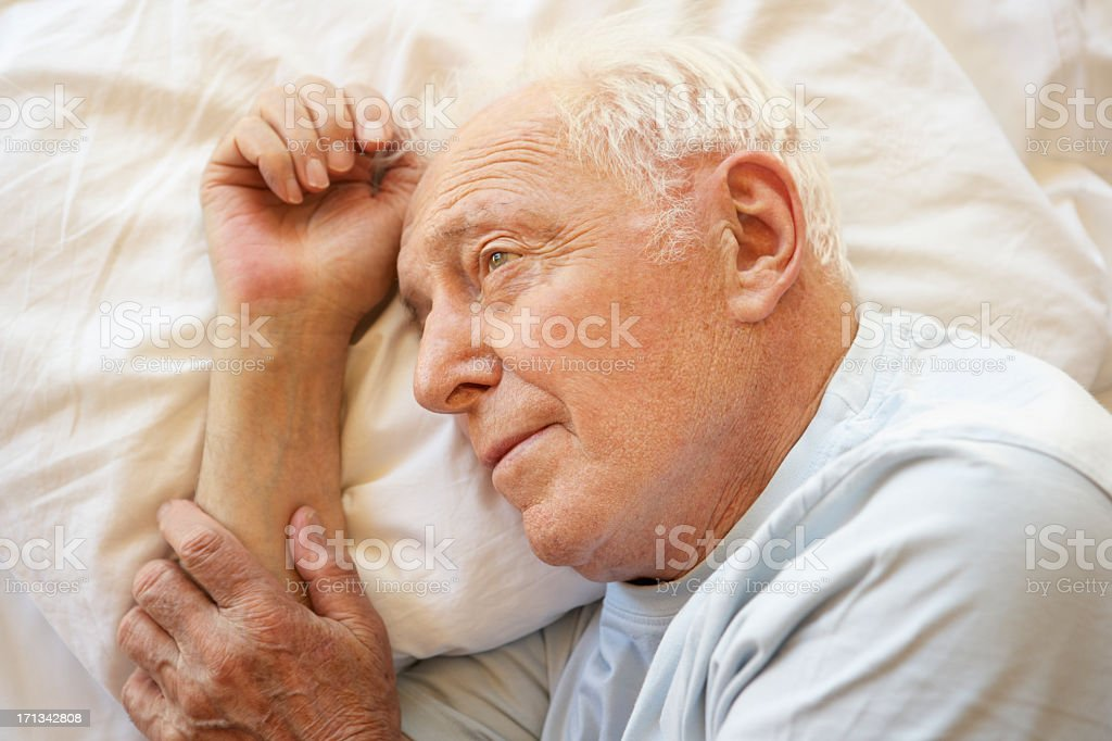 Elderly man resting in a white bed royalty-free stock photo