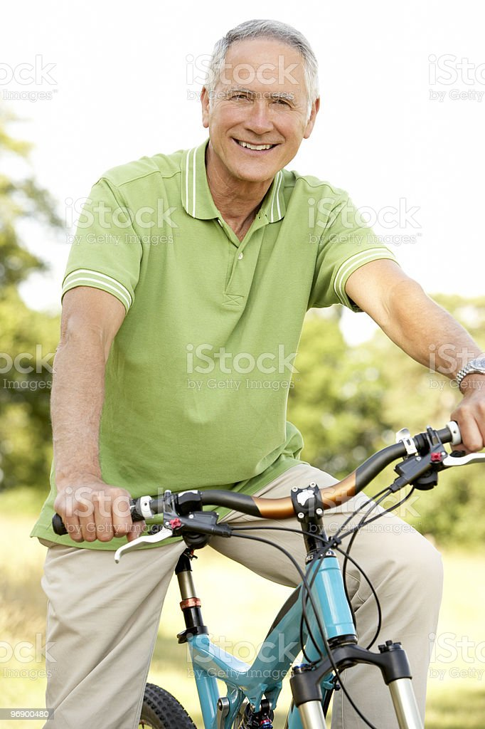 Elderly man riding his bike on a trail in the countryside royalty-free stock photo