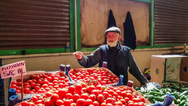 Eskisehir, Turkey - May 25, 2017: Elderly man selling tomatoes and cucumbers in Turkish local bazaar in Eskisehir. stock photo