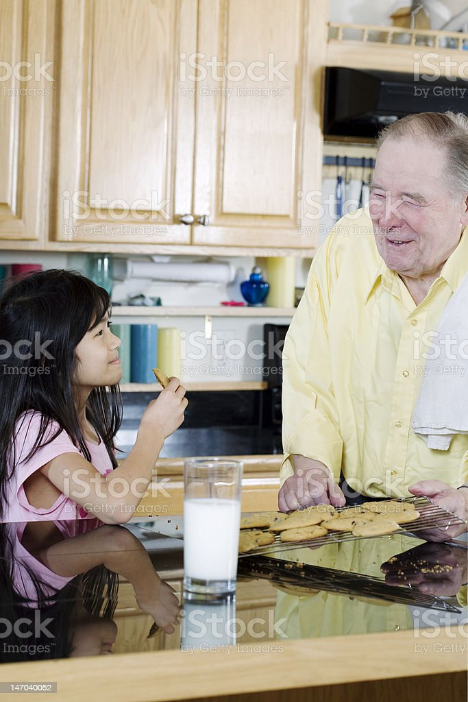 Elderly man sharing cookies with granddaughter royalty-free stock photo