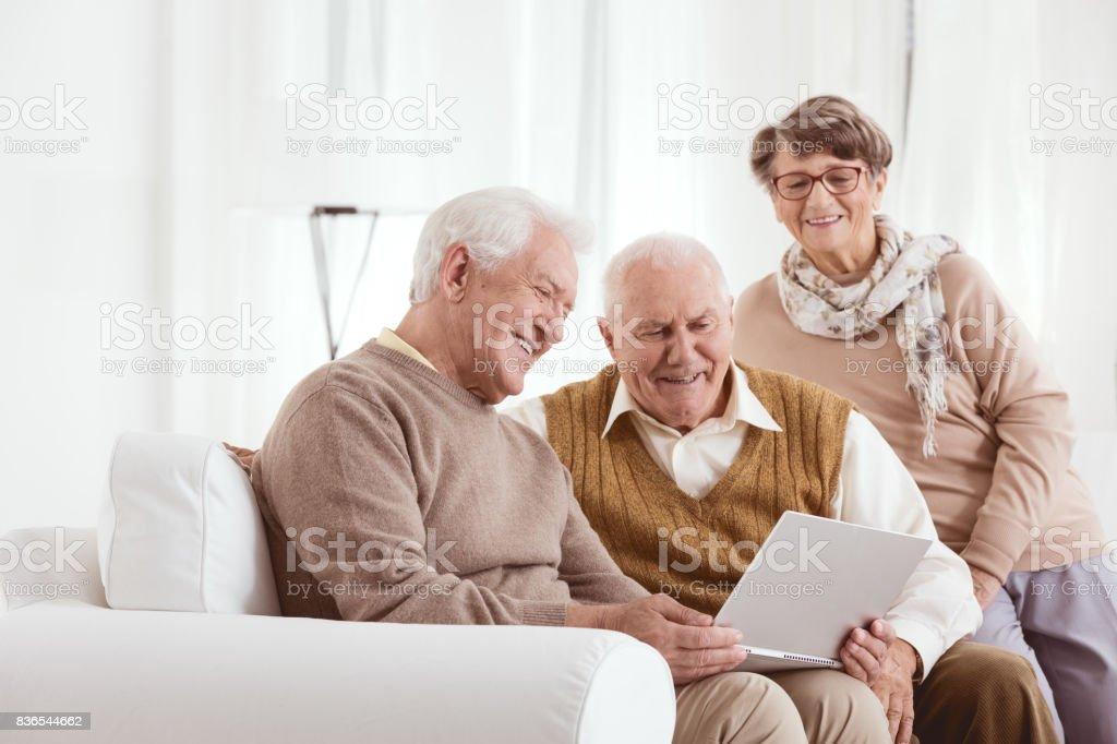 Elderly man showing laptop stock photo