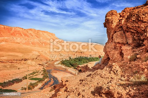 istock Tazelefte, Morocco - October 9, 2015: Elderly man sits on a cliff in the shadow overlooking beautiful view of the desolating valley Ounila River. Amazing Northern African Landscape . Fascinating view from the hill to the valley in Morocco 1096569472