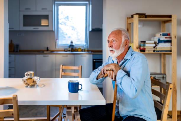 Vieil homme s'asseyant seul à la maison - Photo