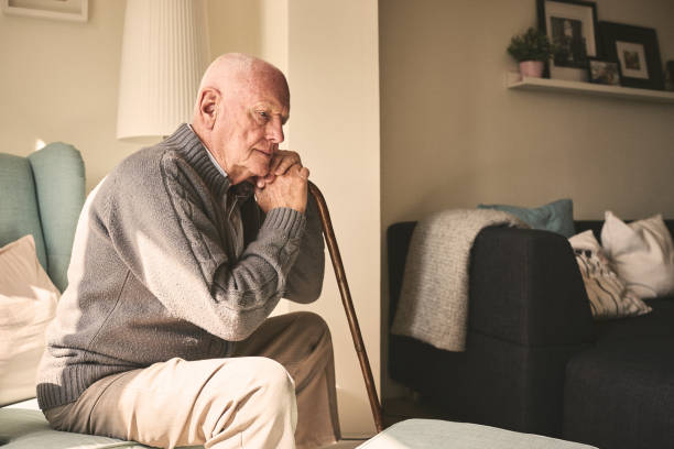 Elderly man sitting alone at home stock photo