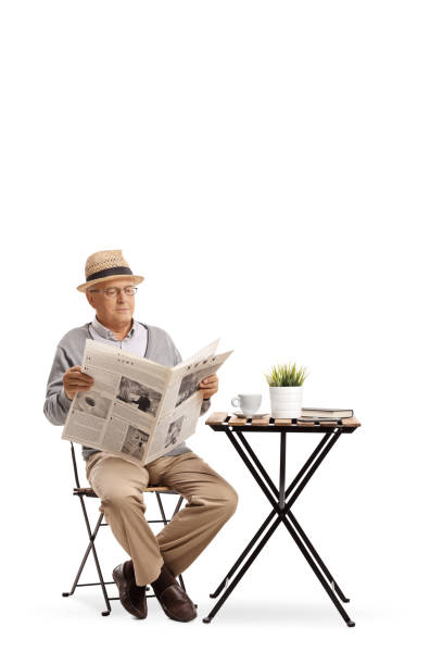 Elderly man sitting at a coffee table reading a newspaper stock photo