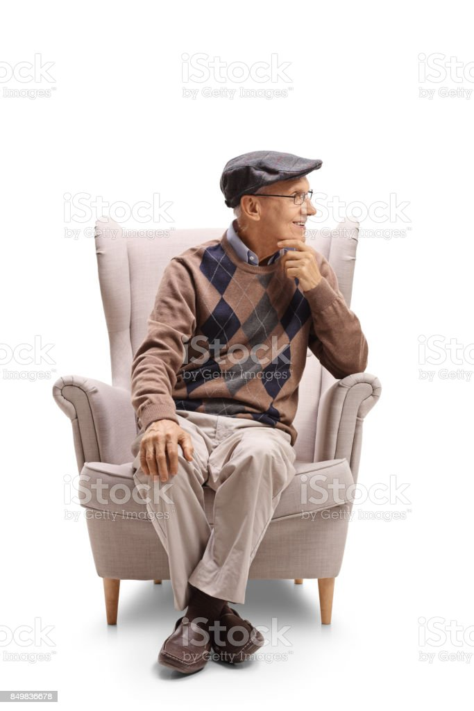 Elderly man sitting in an armchair and looking away stock photo