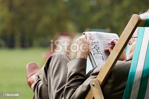A senior gentle man relaxing and doing the crossword
