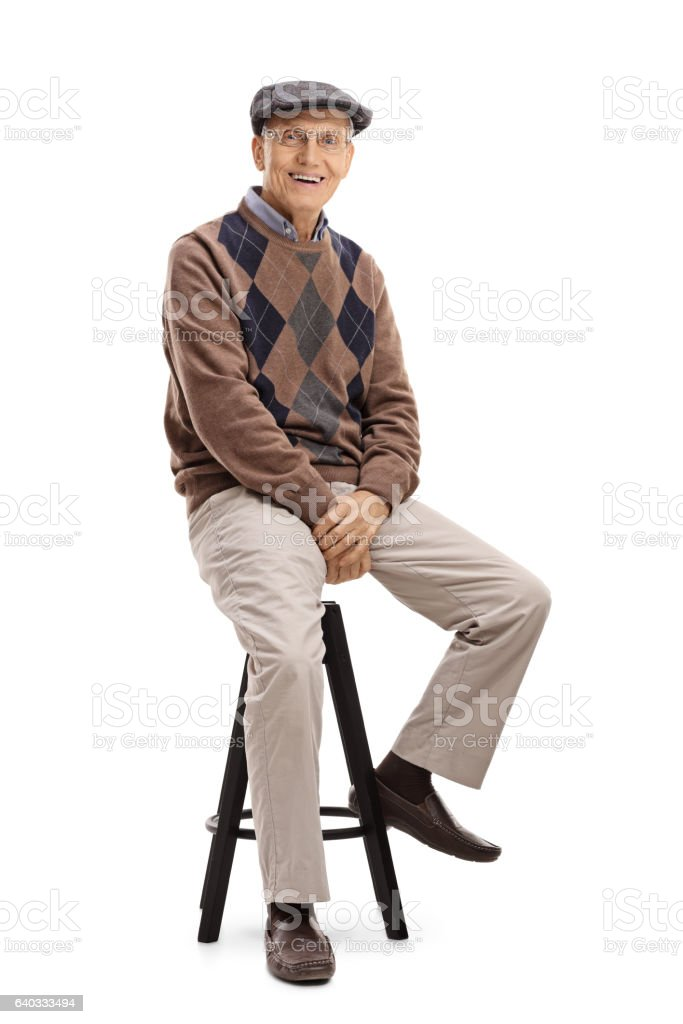 Elderly man sitting on a chair stock photo