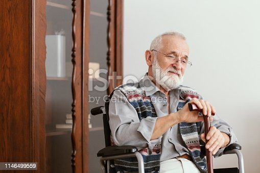 istock Elderly man sitting on a wheelchair and supporting himself with cane 1146499559
